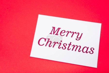 Photo pour Vue du dessus de la carte blanche joyeux Noël sur fond rouge - image libre de droit