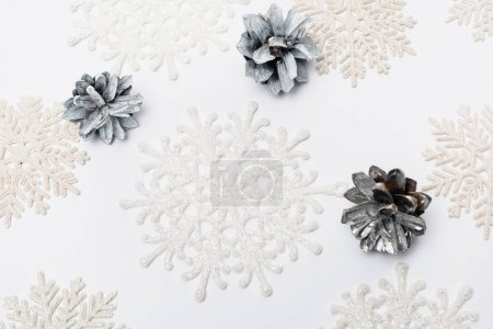 Photo for Top view of winter snowflakes and cones on white background - Royalty Free Image