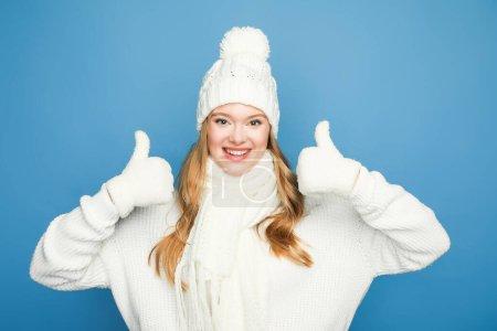Photo pour Heureuse blonde belle femme en tenue blanche d'hiver montrant pouces sur fond bleu - image libre de droit