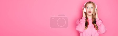 shocked beautiful woman listening music in headphones on pink background, banner