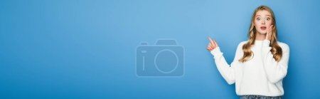 Photo for Shocked blonde beautiful woman in sweater pointing with finger isolated on blue, banner - Royalty Free Image