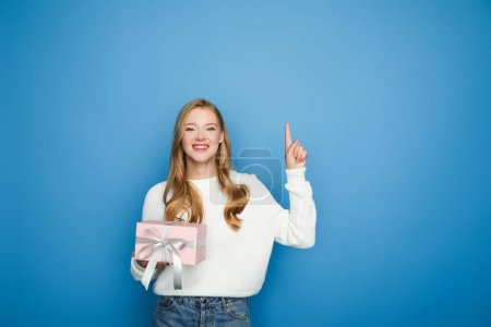 happy blonde beautiful woman in sweater with gift box pointing up isolated on blue