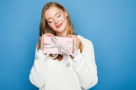 pleased blonde beautiful woman in sweater with gift box isolated on blue