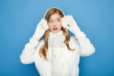 Photo pour Surpris belle femme en tenue blanche d'hiver isolé sur bleu - image libre de droit