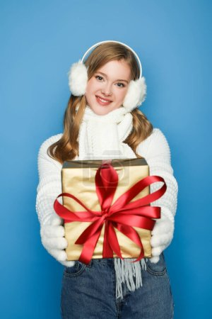 smiling beautiful woman in winter white outfit giving gift box isolated on blue