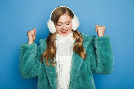 Photo pour Heureuse femme élégante en fausse fourrure verte manteau et cache-oreilles isolés sur bleu - image libre de droit