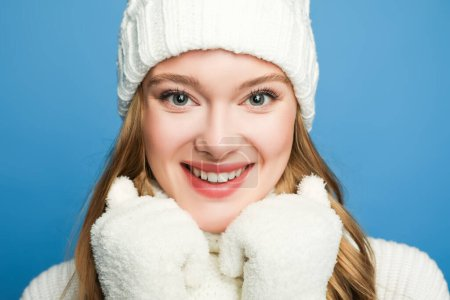 portrait of smiling beautiful woman in winter white outfit isolated on blue