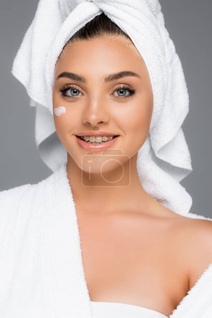 smiling woman with towel on head and cosmetic cream on face isolated on grey