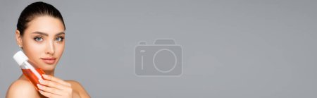 Photo for Beautiful woman with bottle of lotion isolated on grey, banner - Royalty Free Image
