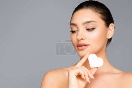 Photo for Woman with naked shoulders and heart shaped cosmetic sponge isolated on grey - Royalty Free Image