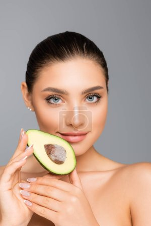 Photo for Woman with naked shoulders and avocado half isolated on grey - Royalty Free Image