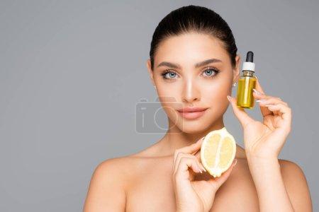 mujer con suero y limón medio aislado en gris