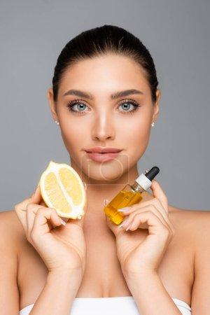 Photo pour Femme avec sérum et citron à moitié isolé sur gris - image libre de droit