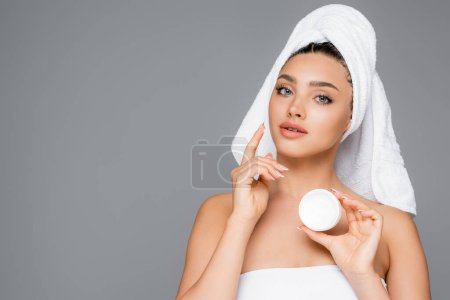 woman with towel on head applying cosmetic cream on face isolated on grey