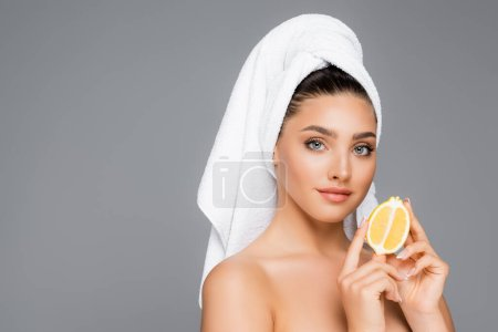 woman with towel on head and lemon isolated on grey