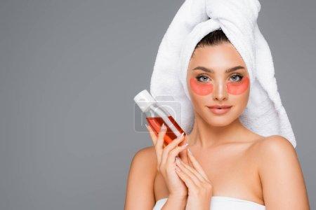 Photo pour Femme avec serviette sur la tête et les yeux tenant lotion isolée sur gris - image libre de droit