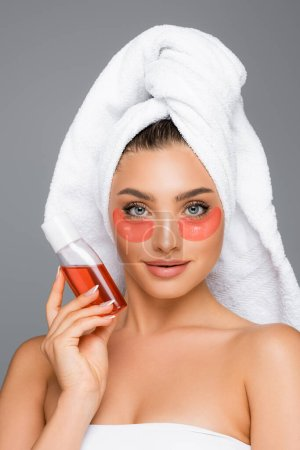 woman with towel on head and eye patches holding lotion isolated on grey