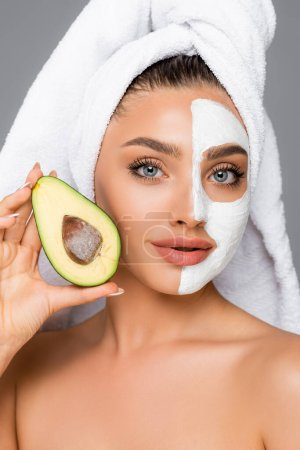 woman with towel on head and clay mask on face holding avocado isolated on grey