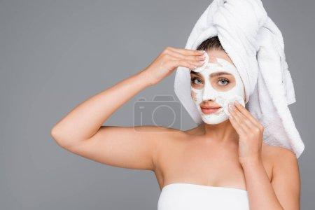 Photo pour Femme avec serviette sur la tête rinçant masque d'argile sur le visage avec des tampons de coton isolé sur gris - image libre de droit