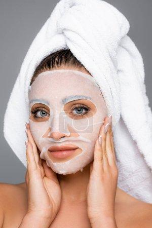 Frau mit Handtuch auf dem Kopf und Maskentuch im Gesicht isoliert auf grau
