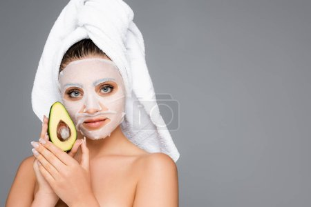 woman with towel on head and mask sheet on face holding avocado isolated on grey