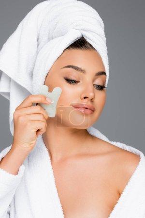 Photo pour Femme avec serviette sur la tête en utilisant gua sha sur le visage isolé sur gris - image libre de droit