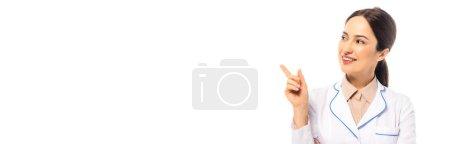 Photo pour Recadrage horizontal d'un médecin joyeux pointant du doigt isolé sur blanc - image libre de droit