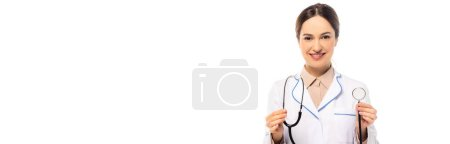 Panoramic shot of doctor in white coat holding stethoscope isolated on white
