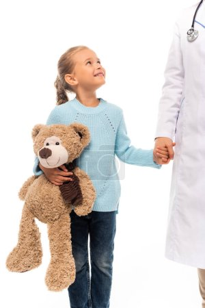 Girl with soft toy holding hand and smiling at pediatrician isolated on white