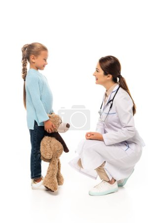 Doctor smiling at kid with soft toy on white background