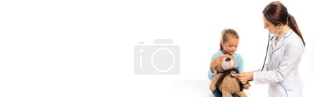 Photo for Panoramic shot of smiling doctor examining soft toy near child isolated on white - Royalty Free Image