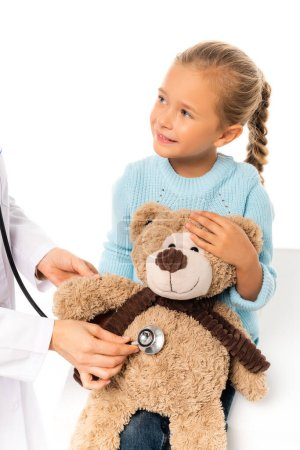 Smiling child holding soft toy near doctor with stethoscope isolated on white