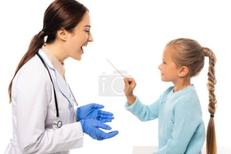 Smiling girl holding stick near pediatrician with open mouth isolated on white