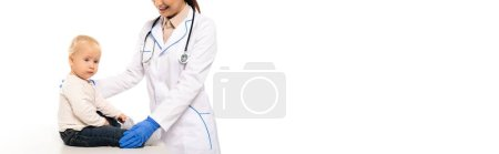 Photo for Panoramic shot of smiling pediatrician in white coat touching toddler boy isolated on white - Royalty Free Image