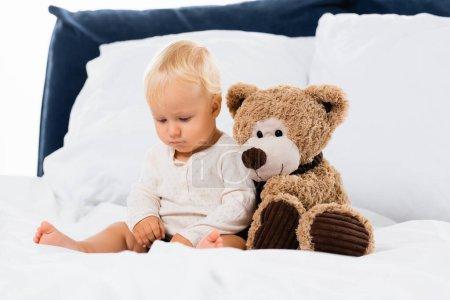 Photo pour Foyer sélectif de tout-petit assis près de jouet doux sur le lit sur fond blanc - image libre de droit