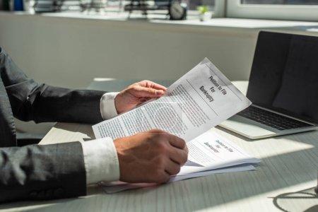 Cropped view of businessman holding petition for bankruptcy, tout en étant assis sur le lieu de travail sur fond flou