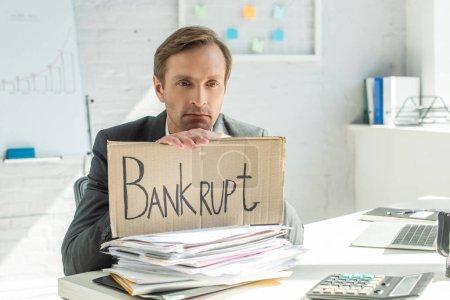 Triste hombre de negocios apoyado en cartón con letras en bancarrota, sentado a la mesa con un montón de papeles sobre fondo borroso