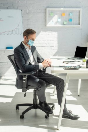 Full length of businessman with clenched hands sitting on office chair at workplace with laptop and stationery on table