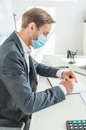 Photo pour Vue latérale de l'homme d'affaires en masque médical, écrit dans un cahier, assis à table sur fond flou - image libre de droit