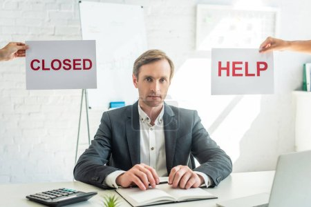 Businessman looking at camera, while sitting at workplace near signs with closed and help lettering on blurred background