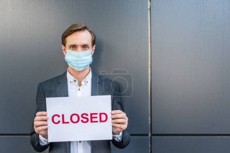 Front view of businessman in medical mask, holding sign with closed lettering on grey textured background