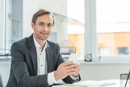 Photo pour Homme d'affaires positif avec smartphone regardant la caméra, tout en s'asseyant sur le lieu de travail avec fenêtre floue en arrière-plan - image libre de droit