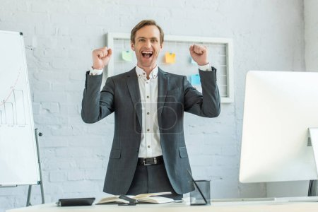 Photo for Front view of excited businessman with yeah gesture looking at camera, while standing near workplace in office - Royalty Free Image