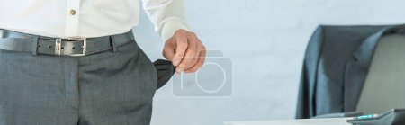 Cropped view of businessman showing empty pocket on blurred background, banner