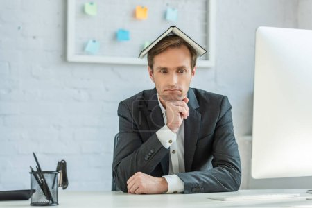 Photo for Upset businessman with notebook on head, sitting at workplace with blurred mesh organizer on background - Royalty Free Image
