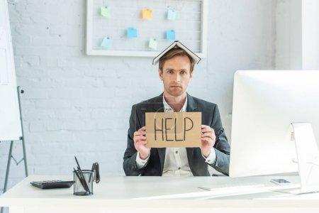Triste hombre de negocios con cuaderno en la cabeza, sosteniendo cartón con letras de ayuda, mientras está sentado en el lugar de trabajo