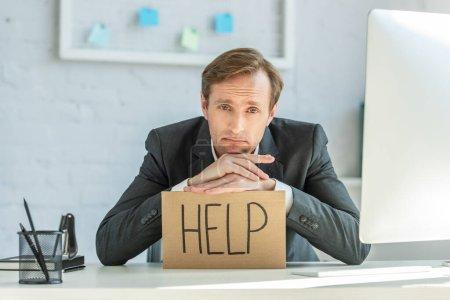 Photo pour Homme d'affaires déçu appuyé sur le carton avec lettrage d'aide, assis sur le lieu de travail sur fond flou - image libre de droit