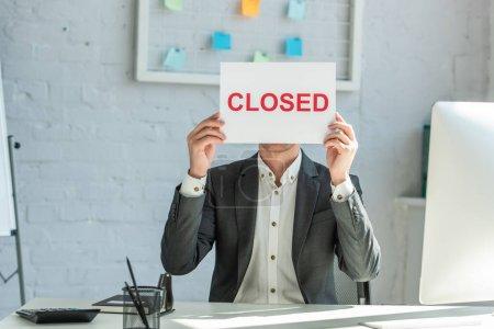 Photo pour Homme d'affaires tenant signe avec lettrage fermé, assis sur le lieu de travail - image libre de droit