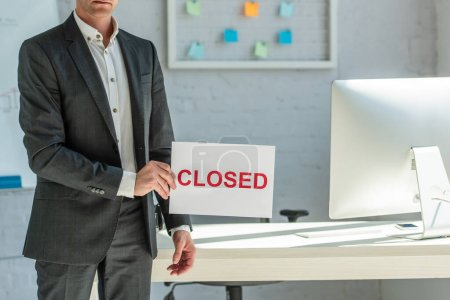 Cropped view of businessman holding sign with closed lettering, while standing near workplace on blurred background