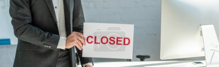 Cropped view of businessman holding sign with closed lettering, while standing near workplace on blurred background, banner